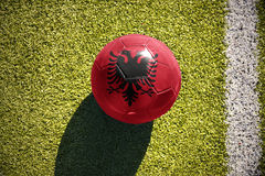 Football ball with the national flag of albania lies on the field. Football ball with the national flag of albania lies on the green field near the white line stock images