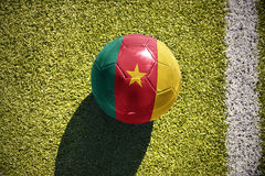 Football ball with the national flag of cameroon lies on the field Stock Image
