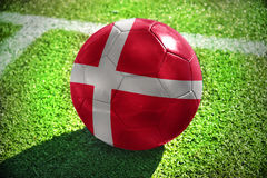 Football ball with the national flag of denmark lies on the green field Royalty Free Stock Images