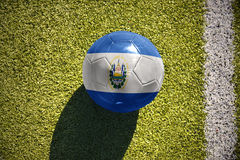 Football ball with the national flag of el salvador lies on the field Royalty Free Stock Photos