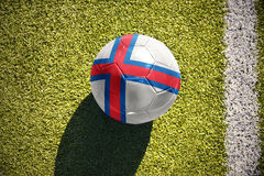 Football ball with the national flag of faroe islands lies on the field Royalty Free Stock Image