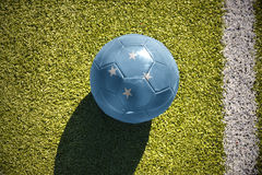 Football ball with the national flag of Federated States of Micronesia lies on the field Stock Photo