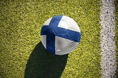 Football ball with the national flag of finland lies on the field Stock Photography