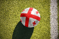 Football ball with the national flag of georgia lies on the field. Football ball with the national flag of georgia lies on the green field near the white line Royalty Free Stock Images