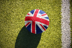 Football ball with the national flag of great britain lies on the field. Football ball with the national flag of great britain lies on the green field near the Stock Photos