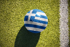 Football ball with the national flag of greece lies on the field Stock Photos