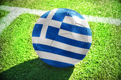 Football ball with the national flag of greece lies on the green field Royalty Free Stock Photography