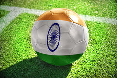 Football ball with the national flag of india. Lies on the green field near the white line Royalty Free Stock Images