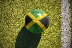 Football ball with the national flag of jamaica lies on the field Royalty Free Stock Photo