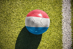Football ball with the national flag of luxembourg lies on the field Stock Image