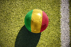 Football ball with the national flag of mali lies on the field. Football ball with the national flag of mali lies on the green field near the white line Stock Images