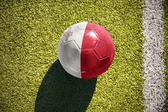 Football ball with the national flag of malta lies on the field. Football ball with the national flag of malta lies on the green field near the white line Royalty Free Stock Photos