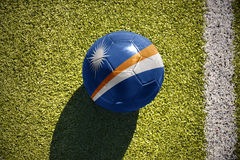 Football ball with the national flag of Marshall Islands lies on the field Royalty Free Stock Photos