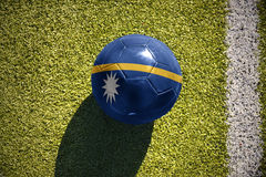 Football ball with the national flag of Nauru lies on the field Royalty Free Stock Photos