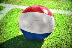 Football ball with the national flag of netherlands lies on the green field Royalty Free Stock Photos