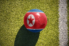 Football ball with the national flag of north korea lies on the field Royalty Free Stock Image