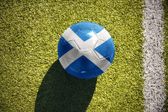 Football ball with the national flag of scotland lies on the field royalty free stock photos