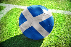 Football ball with the national flag of scotland lies on the green field Royalty Free Stock Image