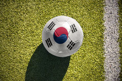 Football ball with the national flag of south korea lies on the field. Football ball with the national flag of south korea lies on the green field near the white royalty free stock photo