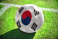 Football ball with the national flag of south korea. Lies on the green field near the white line royalty free stock photos