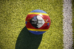 Football ball with the national flag of swaziland lies on the field Stock Photos