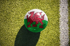 Football ball with the national flag of wales lies on the field Royalty Free Stock Photo