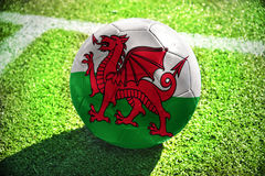 Football ball with the national flag of wales lies on the green field Stock Photography