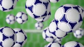 Football balls falling against football gate and green grass field. 4K seamless loop, ProRes clip stock video footage