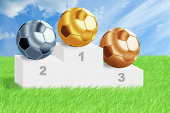 Football balls on podium among green grass. Stock Images