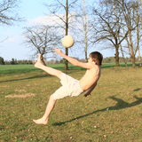 Football. Barefoot boy - teenager playing football with white  ball on meadow Royalty Free Stock Images
