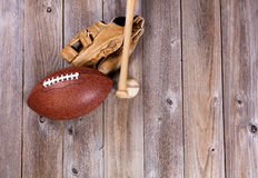 Football and baseball equipment on rustic wooden boards Royalty Free Stock Photo