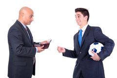 Football bet. Dispeased businessman paying a lost bet to a happy rival over a football game Stock Photo