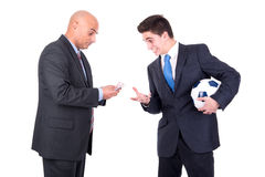 Football bet. Dispeased businessman paying a lost bet to a happy rival over a football game Stock Image