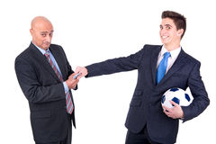 Football bet. Dispeased businessman paying a lost bet to a happy rival over a football game Royalty Free Stock Photos