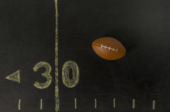 Football on the black field near 30 yards line Royalty Free Stock Photos