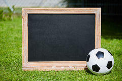 Football and blackboard on the grass of the pitch Royalty Free Stock Photo
