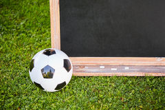 Football and blackboard on the grass of the pitch Royalty Free Stock Images
