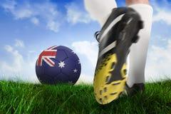 Football boot kicking australia ball. Composite image of football boot kicking australia ball against field of grass under blue sky Stock Images