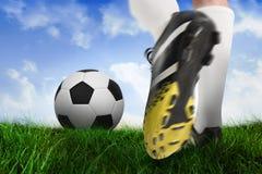 Football boot kicking ball. Composite image of football boot kicking ball against field of grass under blue sky Stock Photos