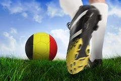 Football boot kicking belgium ball. Composite image of football boot kicking belgium ball against field of grass under blue sky Royalty Free Stock Photos