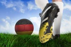 Football boot kicking belgium ball. Composite image of football boot kicking belgium ball against field of grass under blue sky Stock Photo