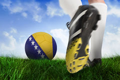 Football boot kicking bosnia ball. Composite image of football boot kicking bosnia ball against field of grass under blue sky Stock Photos