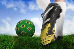 Football boot kicking brasil ball. Composite image of football boot kicking brasil ball against field of grass under blue sky Stock Photos