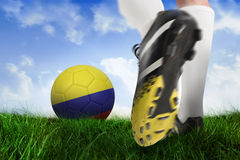 Football boot kicking colombia ball. Composite image of football boot kicking colombia ball against field of grass under blue sky Stock Photography