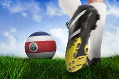 Football boot kicking costa rica ball. Composite image of football boot kicking costa rica ball against field of grass under blue sky Royalty Free Stock Photo