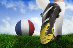 Football boot kicking france ball. Composite image of football boot kicking france ball against field of grass under blue sky Royalty Free Stock Images