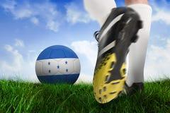 Football boot kicking honduras ball. Composite image of football boot kicking honduras ball against field of grass under blue sky Stock Photography