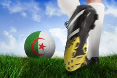 Football boot kicking iran ball. Composite image of football boot kicking iran ball against field of grass under blue sky Stock Photography