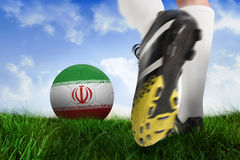 Football boot kicking iran ball. Composite image of football boot kicking iran ball against field of grass under blue sky Royalty Free Stock Image