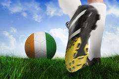 Football boot kicking ivory coast ball. Composite image of football boot kicking ivory coast ball against field of grass under blue sky Royalty Free Stock Photography